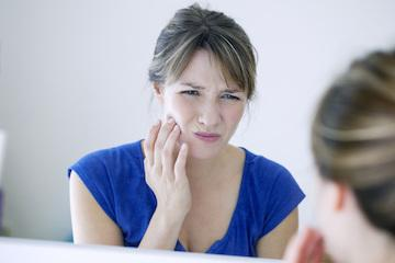 Woman with bad tooth pain in need of custom nightguard in Webster Groves